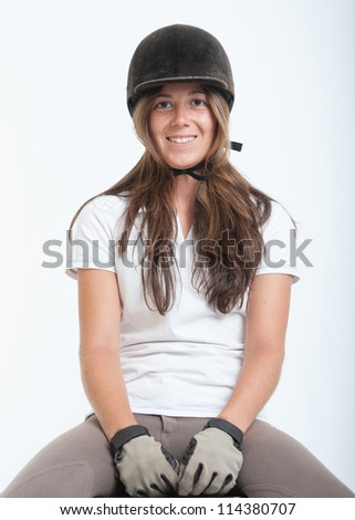 Young woman dressed in horse riding clothes