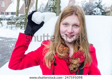 Young woman dressed in red holding snowball - stock photo
