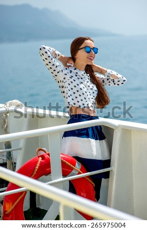 Young woman dressed in shirt and skirt sailing on cruise liner or ferry with sea and mountain background - stock photo