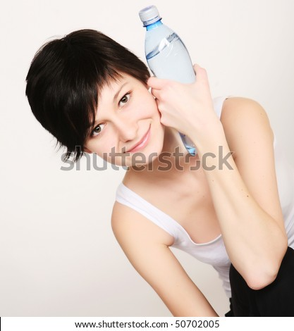 Young woman dressed in sportswear holding a water bottle