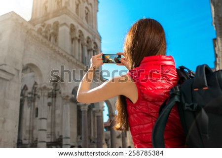 Young woman dressed in sportswear with smart phone traveling in the old city center - stock photo