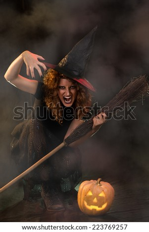 Young woman dressed like a witch. She is in dark with broom and pumpkin.