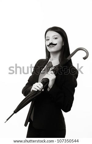 young woman dressed up in a man's suit and tie wearing a fake mustache holding a umbrella - stock photo