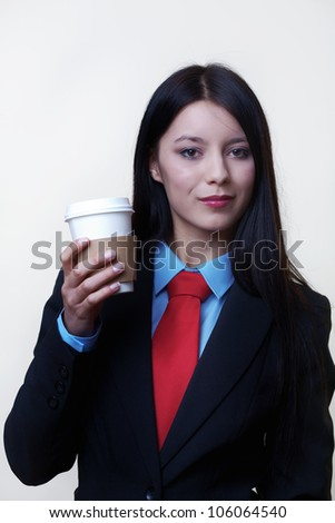 young woman dressed up in a man suit and tie holding a paper coffee cup - stock photo
