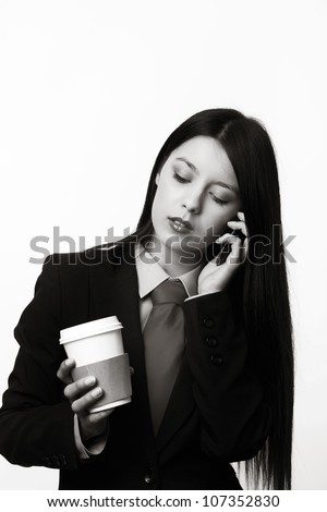 young woman dressed up in a man suit and tie holding a paper coffee cup and on the phone - stock photo