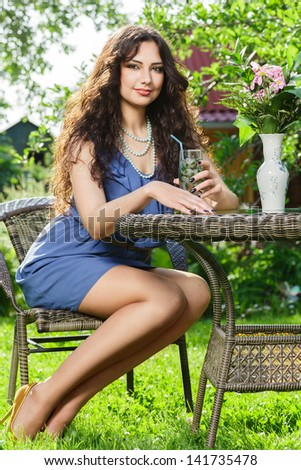 Young woman drink mojito cocktail full body portrait - stock photo