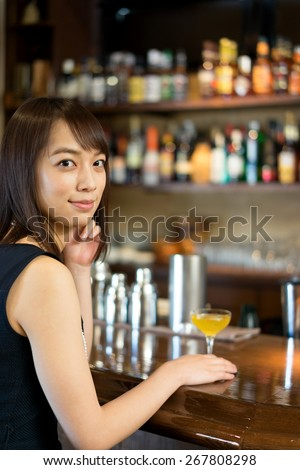 young woman drinking a cocktail at bar - stock photo
