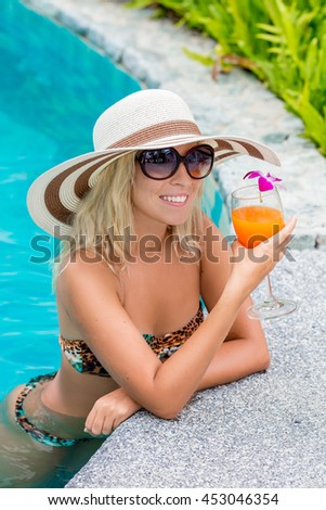 young woman drinking a cocktail in the pool