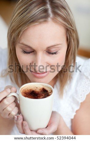 Young woman drinking a coffee sitting on a sofa at home - stock photo
