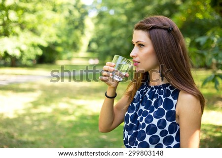 young woman drinking a glass of water outdoors - stock photo