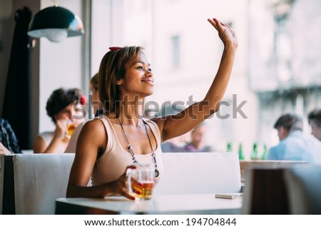 Young woman drinking beer in bar and waving - stock photo