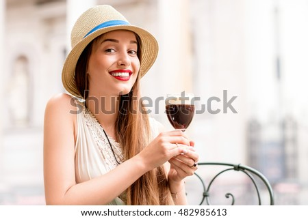 Young woman drinking bicerin traditional Italian coffee made of espresso, chocolate and whole milk sitting outdoors in Turin city