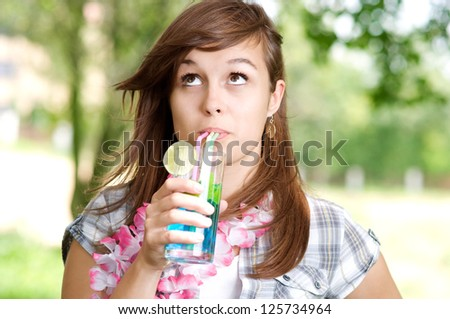 Young woman drinking blue curacao cocktail - stock photo