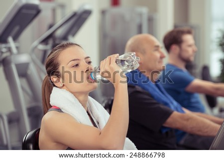 Young woman drinking bottled water in a gym as she pauses while working out on the equipment to quench her thirst - stock photo