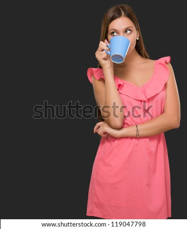 Young Woman Drinking Coffee against a black background - stock photo
