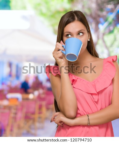 Young Woman Drinking Coffee at a restaurant - stock photo