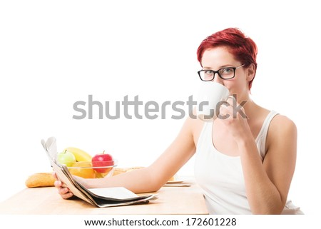 young woman drinking coffee at breakfast and  reading newspaper on white background - stock photo