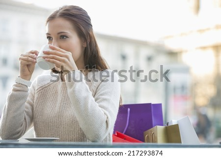 Young woman drinking coffee at sidewalk cafe - stock photo