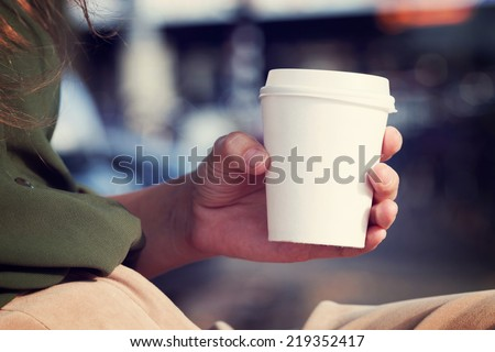 Young woman drinking coffee from disposable cup