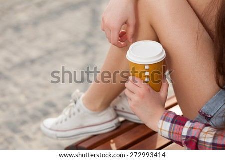 Young woman drinking coffee in a paper cup - stock photo