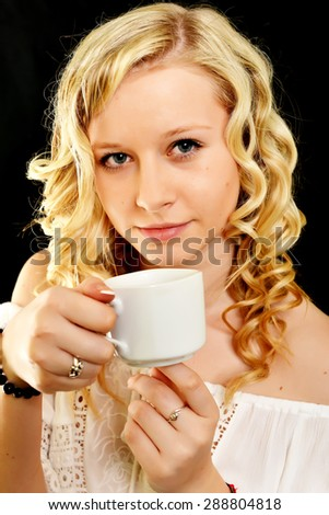 Young woman drinking coffee in a trendy cafe - stock photo