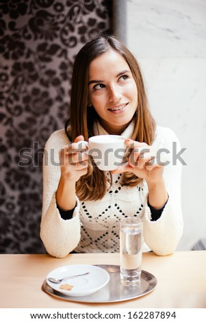 Young woman drinking coffee in cafe and daydreaming - stock photo