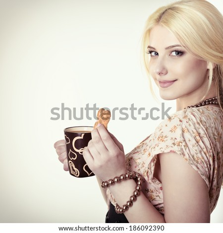 Young woman drinking coffee latte and eating cookie. Toned. - stock photo