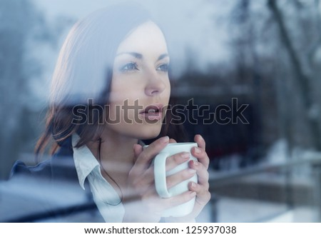 Young woman drinking coffee looking through the window - stock photo