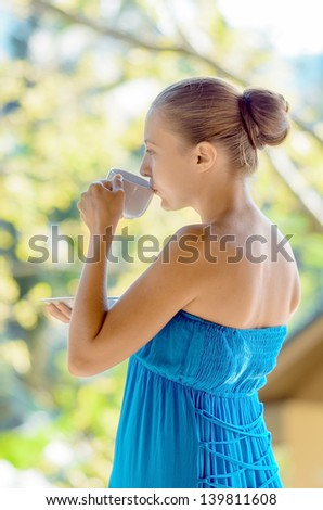 Young woman drinking coffee on morning terrace.