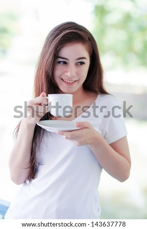 young woman drinking coffee outdoor on balcony - stock photo