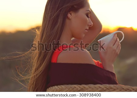 Young woman drinking coffee, tea in the sunshine. Sunset, soft lights. - stock photo