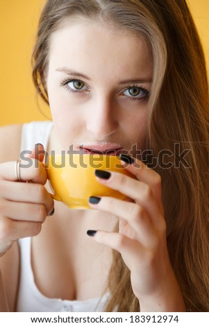 Young woman drinking coffee with a froth moustach