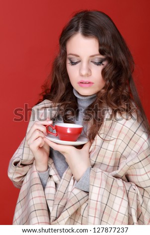 Young woman drinking coffee with red cup