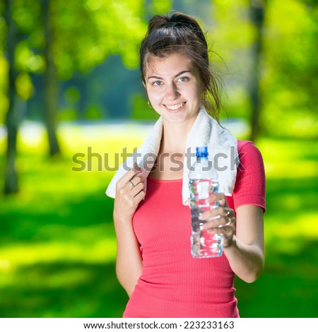 Young woman drinking cold mineral water after sport fitness exercise at green summer park