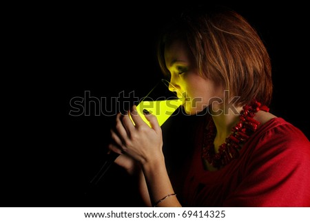 young woman drinking from a glass of glowing liquid
