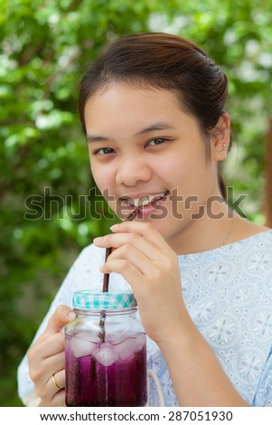 young woman drinking fruit juice, on green nature background - stock photo