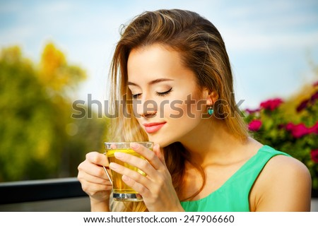 Young Woman Drinking Green Tea Outdoors. Summer Background. Shallow Depth of Field. - stock photo
