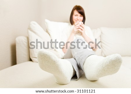 Young woman drinking hot coffee and resting her feet - stock photo