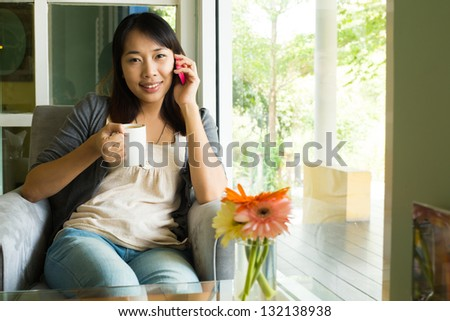 Young woman drinking  hot coffee and talking on phone in  sidewalk cafe - stock photo