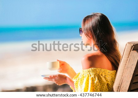 Young woman drinking hot coffee enjoying beach view. Beautiful woman relax during exotic vacation on the beach enjoying sweet coffee - stock photo