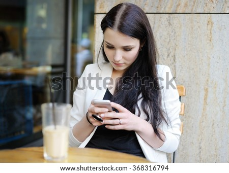 Young woman drinking ice coffee and using her mobile phone in a outdoor cafe