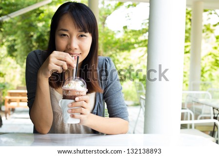 Young woman drinking ice coffee at restaurant