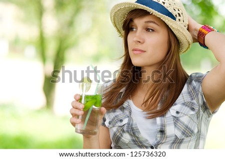 Young woman drinking mojito - stock photo