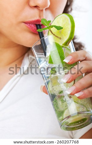 Young woman drinking mojito on white background