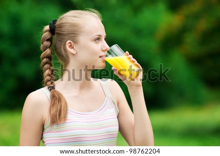 Young woman drinking orange juice after outdoor fitness exercise - stock photo