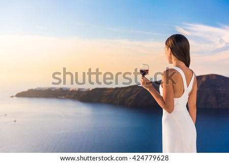 Young woman drinking red wine on outdoor terrace watching beautiful sunset view of Mediterranean Sea. Female in white sundress on summer Europe travel vacation in Santorini, Greece. - stock photo
