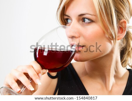 Young woman drinking red wine - studio shot