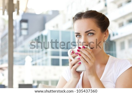 Young woman drinking tea in a cafe outdoors - stock photo