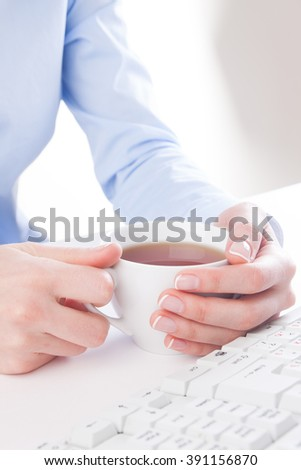 Young woman drinking tea in the workplace - stock photo
