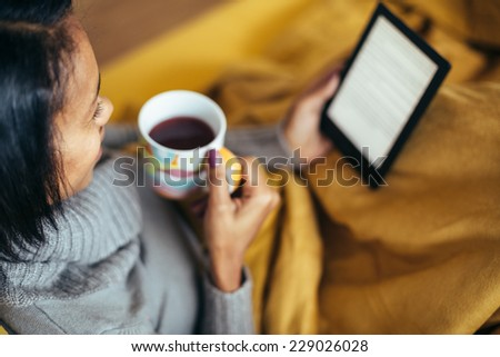 Young woman drinking tea reading ebook on couch - stock photo